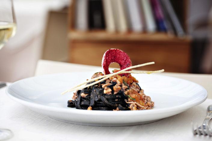 Elegante fotografia di linguine al nero di seppie. Fotografo per ristoranti food piatti gourmet
