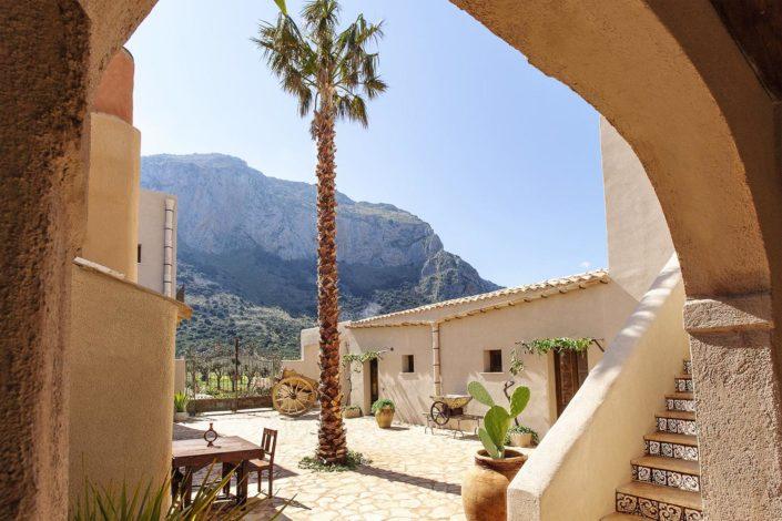 Fotografia di un antico baglio in Sicilia con una palma altissima e le pale di fichidindia