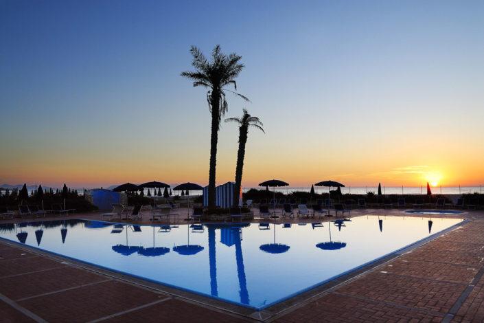 Immagine della piscina di un Hotel a Trapani con le palme, il mare ed il tramonto