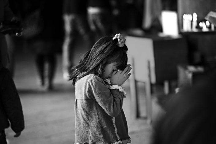 Foto Reportage in bianco e nero realizzate in Giappone, Usi e costumi di un popolo, qui in foto una bambina china in preghiera