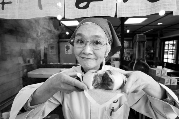 Foto Reportage in bianco e nero realizzate in Giappone, Usi e costumi di un popolo, qui in foto una locandiera offre una polpetta giapponese a Takayama