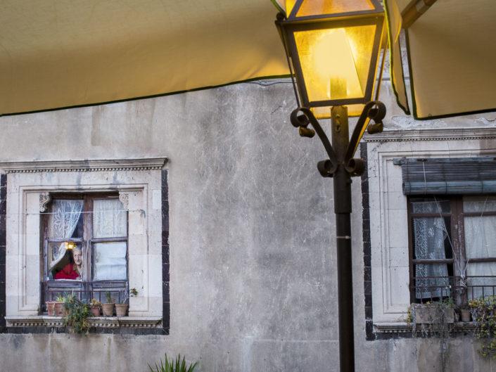 Street Photography. Fotografia a colori di una signora anziana alla finestra e lampione acceso in primo piano. Viaggio fotografico in Sicilia tra paesi paesaggi gente e tradizioni tipiche locali.