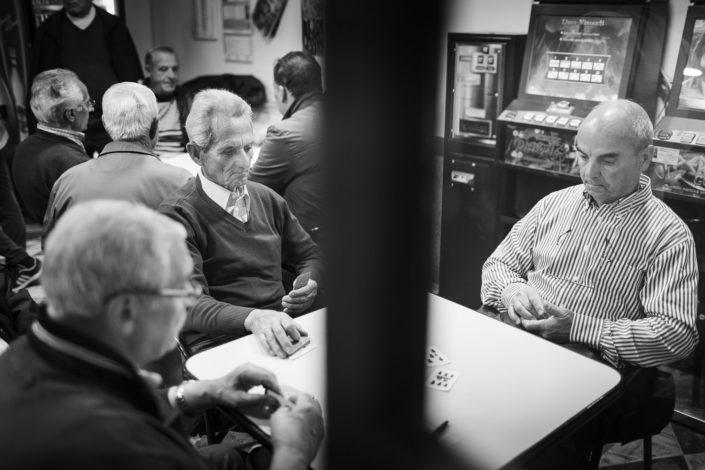 Street Photography. Fotografia in bianco e nero di gente che gioca con le carte siciliane. Viaggio fotografico in Sicilia tra paesi paesaggi gente e tradizioni tipiche locali.
