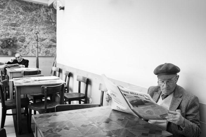 Street Photography. Fotografia in bianco e nero di un siciliano con il corriere della sera. Viaggio fotografico in Sicilia tra paesi paesaggi gente e tradizioni tipiche locali.