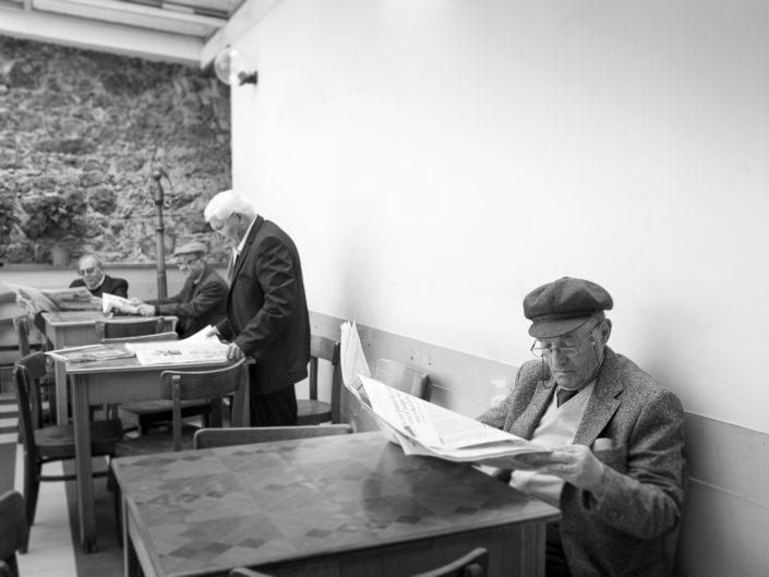 Street Photography. Fotografia in bianco e nero di siciliani che leggono il quotidiano. Viaggio fotografico in Sicilia tra paesi paesaggi gente e tradizioni tipiche locali.