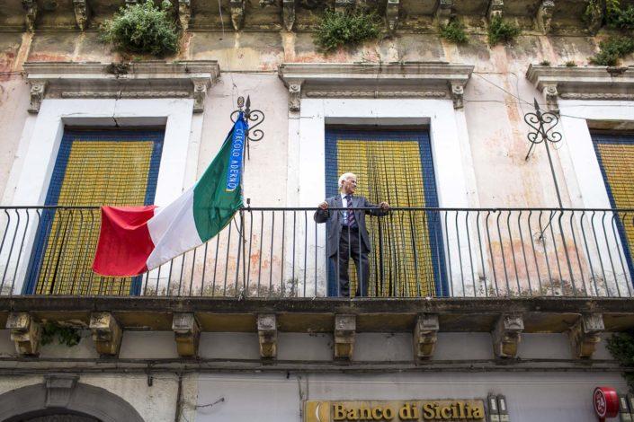 Street Photography. Fotografia a colori di un siciliano affacciato in un balcone ed una bandiera italiana. Viaggio fotografico in Sicilia tra paesi paesaggi gente e tradizioni tipiche locali.