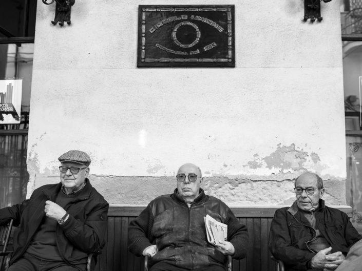 Street Photography. Fotografia in bianco e nero di tre siciliani seduti in una panchina. Viaggio fotografico in Sicilia tra paesi paesaggi gente e tradizioni tipiche locali.