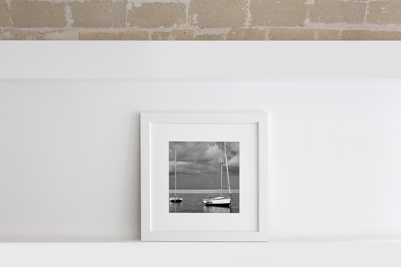 Fotografia in bianco e nero di due barche a vela al mare in formato quadrato con passe-partout e cornice bianca