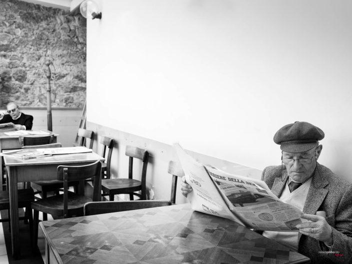 Anziano Siciliano legge giornale al circolo, foto di viaggio